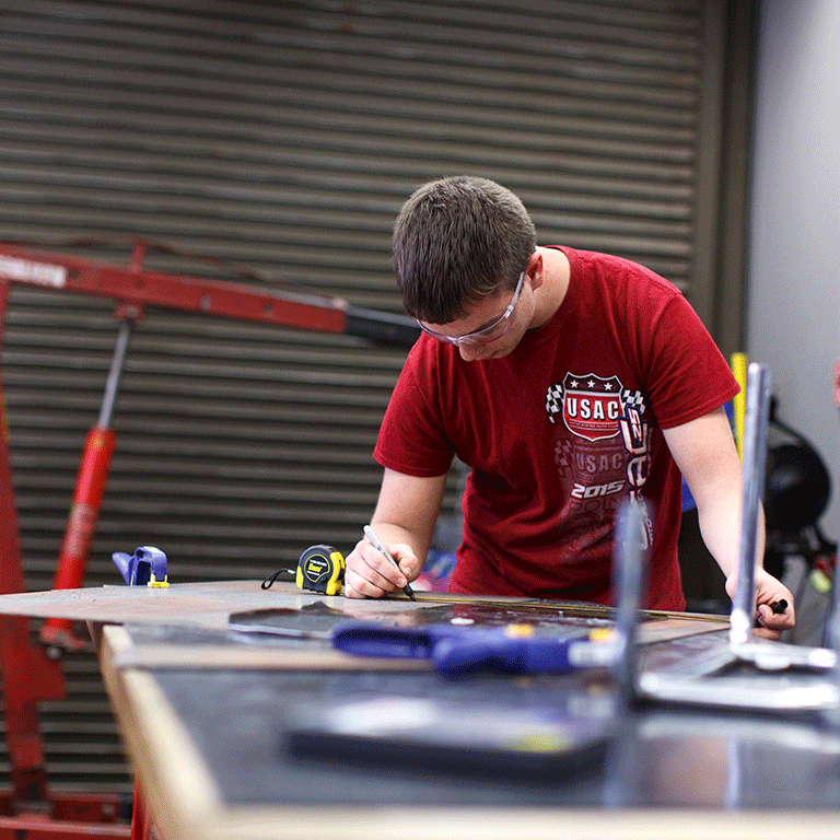A photo of a motorsports engineering student working in the motorsports garage.