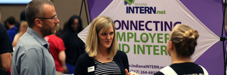 A photo of a student speaking with employers at a career event on campus.